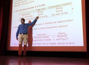 """Alessandro Strumia dari Universitas Pisa, sedang berceramah di sebuah konferensi tahun 2013, turut mengembangkan teori kesimetrian skala fisika partikel yang disebut """"agravitasi"""". (Thomas Lin/Quanta Magazine)"""